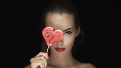 Attractive young brunette woman  licking heart shaped lollipop Stock Footage
