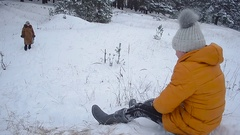 Happy child riding with snowy hills in winter park, a girl is laughing in snow a Stock Footage