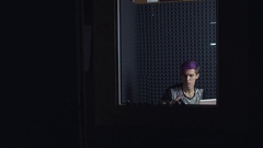 Video blogger with purple hair making video review about something in web studio Stock Footage