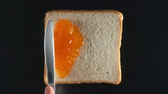 Human hand spreads an apricot jam on a bread Stock Footage