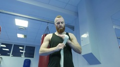 Fighter preparing for training, wrapping hands with boxing wraps Stock Footage