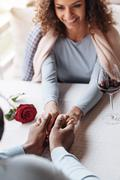 Amused African American couple holding hands in the restaurant Stock Photos