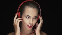 Brunette young woman listening to music on bluetooth headphones  Stock Footage