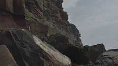 Sandstone Cliffs Sunny Day with Rocks in Foreground, Seagulls and a Clear Sky Stock Footage