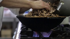 Mushrooms are fried in a wok in the kitchen Stock Footage