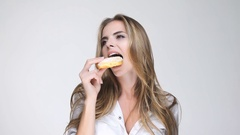 Beautiful young woman with long hair  biting sweet donut Stock Footage