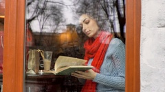 Absorbed girl reading book and drinking coffe by the cafe's window, steadycam sh Stock Footage