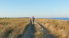4K. Adult  slender man walk near road near sea in summer time and smile Stock Footage