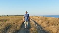 4K. Adult  slender man walk near road near sea in summer time. Back view  Stock Footage