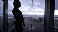 Girl standing at the airport near a large window looking out on the planes that Stock Footage