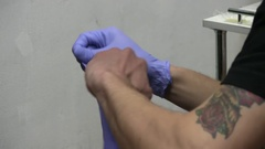 A Tattoo Artist Is Putting On His Gloves Before Work Stock Footage