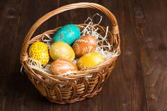 Easter eggs in basket on color wood background Stock Photos