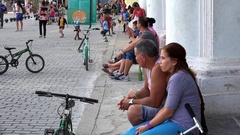 Local cubans are sitting on colonnade steps on the Plaza Vieja. Old Havana Stock Footage