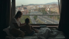 View of mother lying on the bed with small son against huge panoramic window and Stock Footage