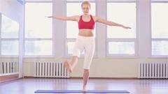 Young fit woman practicing yoga asana garudasana Stock Footage