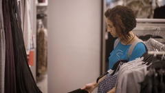 A young girl dressed in a blue T-shirt and gray backpack on the back to choose Stock Footage