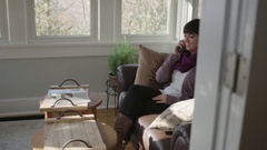 Tracking shot of young lady smiling and talking on cell phone Stock Footage