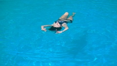 Adorable fit woman in black swimsuit is relaxing luying on the water. Young Stock Footage