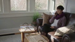 Wide tracking shot of young lady having a cordial conversation on her home phone Stock Footage