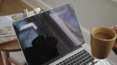 Close up shot of laptop screen with coffee out of focus in foreground Stock Footage