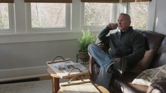 Wide tracking shot of an older man relaxing in a sunroom talking on the phone Stock Footage