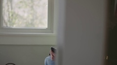 Medium tracking shot of an older man dialing then talking on the phone Stock Footage