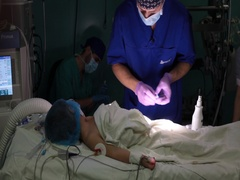The anaesthetist in the mask preparing for surgery the little boy Stock Footage