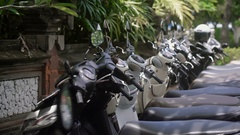Several scooters are parked on the street in a row. Convenient transportation to Stock Footage