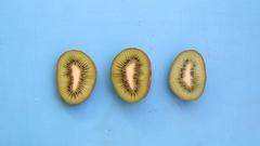 Kiwi fruit on blue background, tasty vegetarian dishes Stock Footage