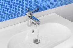 The water flows from faucet. Stock Photos