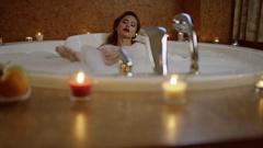 Beautiful woman with cosmetics taking bath with foam Stock Footage