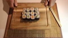 Hands of the waiter are placing the desk with sushi on the table. Hands of the Stock Footage