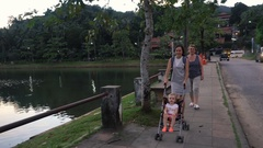 Family walking along embankment with baby girl Stock Footage