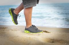 Men's feet in sneakers go on the beach. Stock Photos