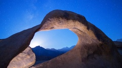 Astro Timelapse of Moonset & Galaxy thru Mobius Arch in Eastern Sierra -Tilt Up- Stock Footage