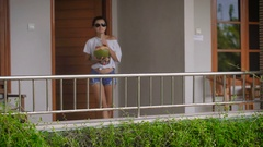 She comes out of her room. She goes on to the veranda. In Bali, great weather Stock Footage