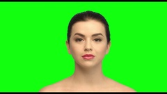 She puts on face cream, brunette on the green screen Stock Footage