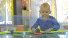 Little boy plaiying air hockey Stock Footage