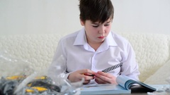 Teen boy collects constructor in room Stock Footage