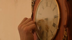 Hand moves clock arrows back - time correction closeup Stock Footage
