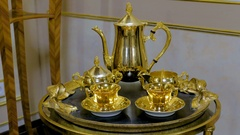Tea set made of gold on the tray. It consists of two mugs, sugar bowls, teapot Stock Footage