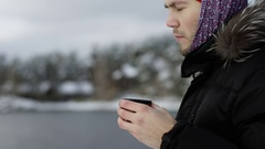Traveler drinks tea at the view of winter lake Stock Footage