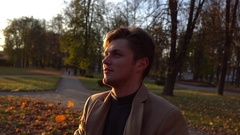 Man looking at sun in autumn park. Young attractive man's portait in park with Stock Footage