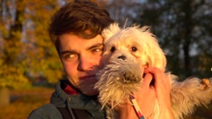 Portrait of young attractive man holding a cute puppy bichon dog in autumn park Stock Footage
