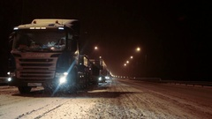 Traffic jam is on wintry federal road M10 at night time. Freight trucks stand Stock Footage