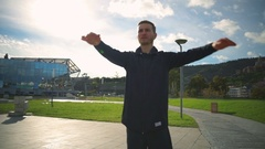 Young fit man warming up and doing body turning exercise in the beautiful park Stock Footage