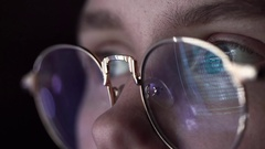 The Machine Code is Reflected in the Hacker's Glasses. Close-up Shot Stock Footage