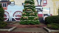 Crane Shot of Christmas Tree and Background of Train Painted on Brick Wall Stock Footage