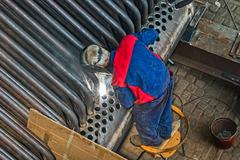 Welder welding metal pipes Stock Photos