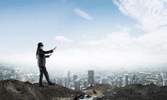 Young businessman in blindfold walking carefully and cityscape at background Stock Photos